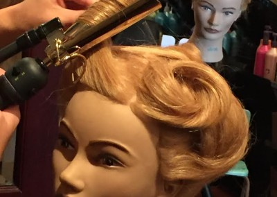 A student of Koko Academy practices curling hair on a mannequin head